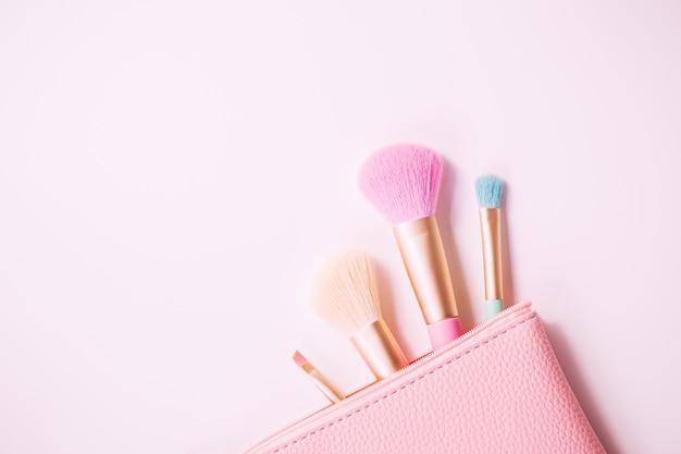 Pincéis de maquiagem com pó na superfície branca