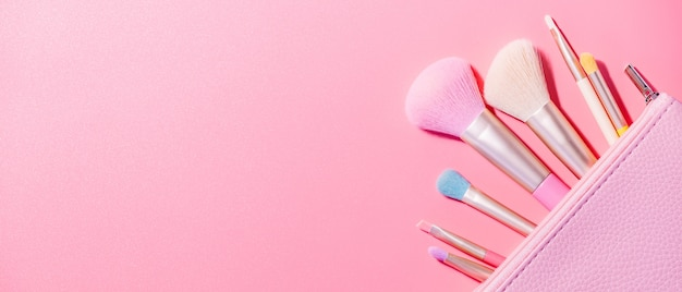 Pincéis de maquiagem com pó na superfície rosa