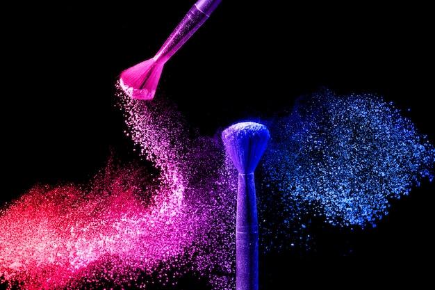 Pincéis de maquiagem com respingos de pó azul e rosa.