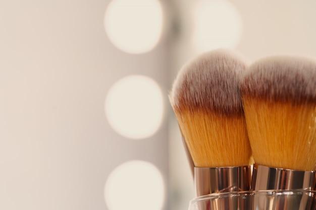 Pincéis de maquiagem. conceito de beleza. luz de fundo.