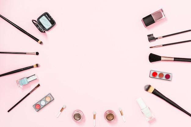Pincéis de maquiagem e cosméticos decorativos em fundo rosa com espaço para escrever o texto