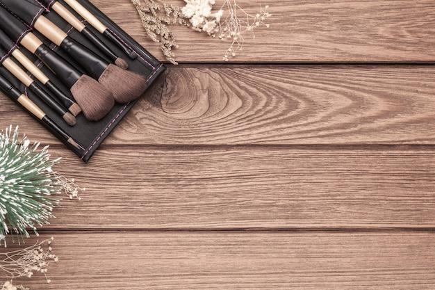 Pincéis de maquiagem e mini pinheiro de natal em fundo de madeira