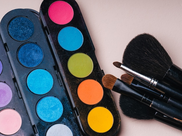 Pincéis de maquiagem e paleta de cores vivas com tons para pintar os olhos