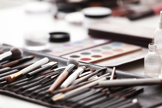 Pincéis de maquiagem e paleta de sombra na mesa. conjunto de artista de rosto profissional