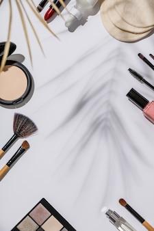 Pincéis de maquiagem e produtos cosméticos em um branco