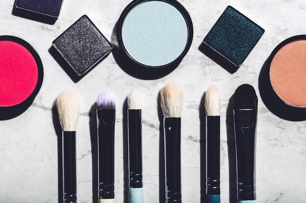 Pincéis de maquiagem e sombras em um fundo de mármore