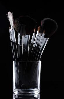 Pincéis de maquiagem em copo de vidro em fundo cinza