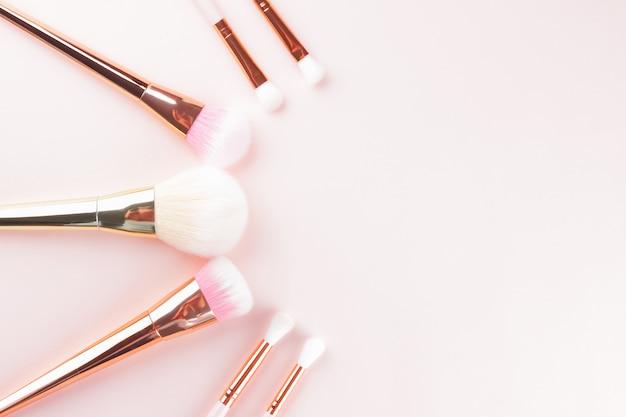 Pincéis de maquiagem em fundo rosa