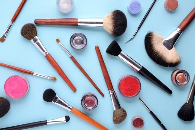 Pincéis de maquiagem em um fundo azul com vista superior em lay plana