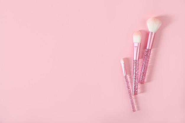 Pincéis de maquiagem em um fundo rosa. lugar para texto