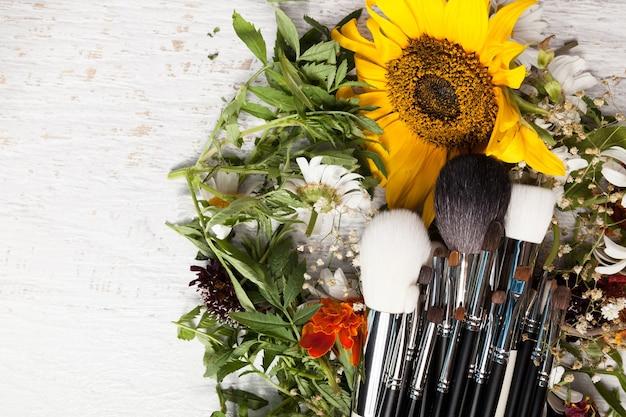 Pincéis de maquiagem em uma pilha de flores silvestres em fundo de madeira