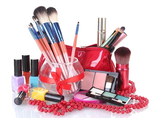Pincéis de maquiagem em vaso de vidro e cosméticos isolados no branco