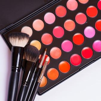 Pincéis de maquiagem no suporte e cosméticos isolados no branco