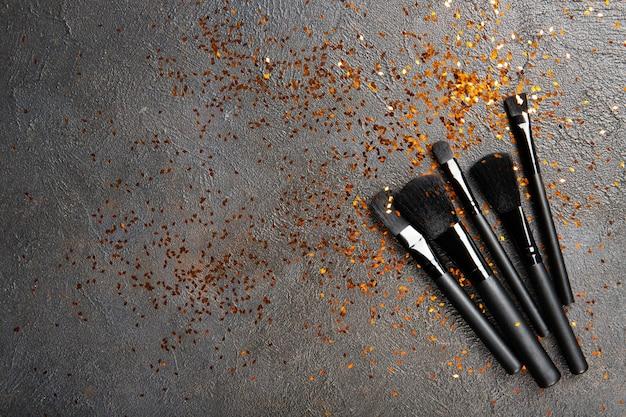 Pincéis de maquiagem preta e brilhos dourados. lugar para texto