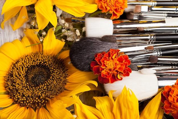 Pincéis de maquiagem profissionais ao lado de lindas flores silvestres em fundo de madeira