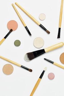 Pincéis de maquiagem profissionais dispostos aleatoriamente, com paleta de sombras de olhos nude, isolados no fundo branco. vista superior, flatlay. o conceito de maquiagem e cosméticos, rosto.