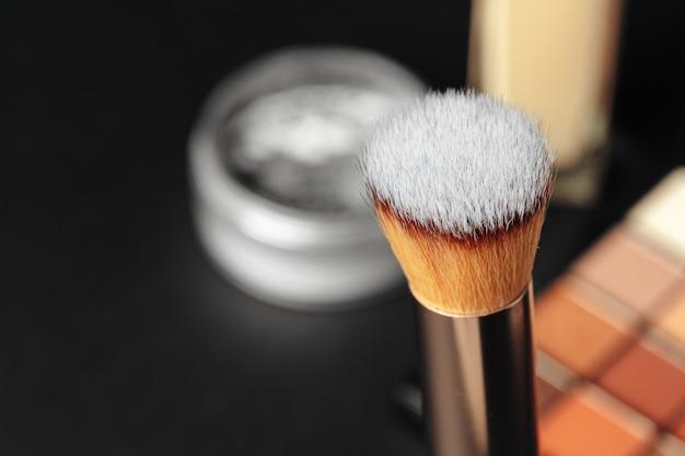 Pincéis de maquiagem profissional e ferramentas, produtos de maquiagem, definido na mesa escura