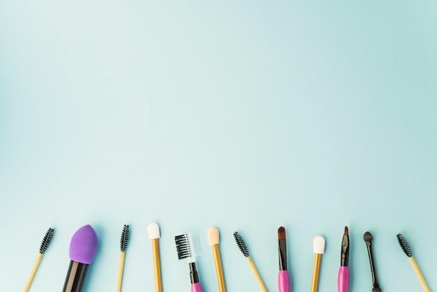 Pincéis de maquiagem profissional e rímel dispostos em uma linha sobre fundo colorido