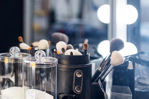 Pincéis de maquiagem profissional na mesa de maquiagem com iluminação de vaidade.