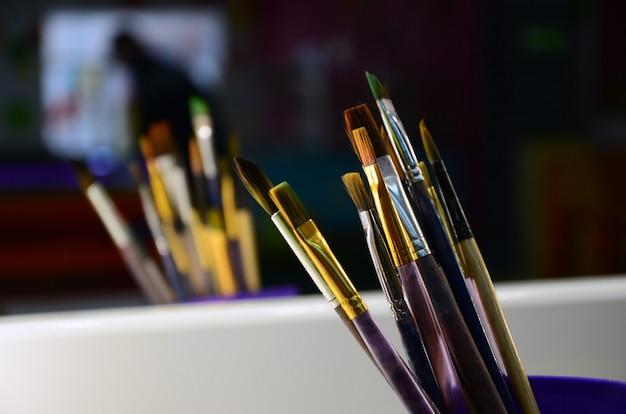 Pincéis de pintura de arte em copo estão localizados no salão de entretenimento infantil no espelho.