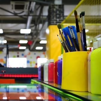 Pincéis de pintura de arte em copo estão localizados no salão de entretenimento infantil