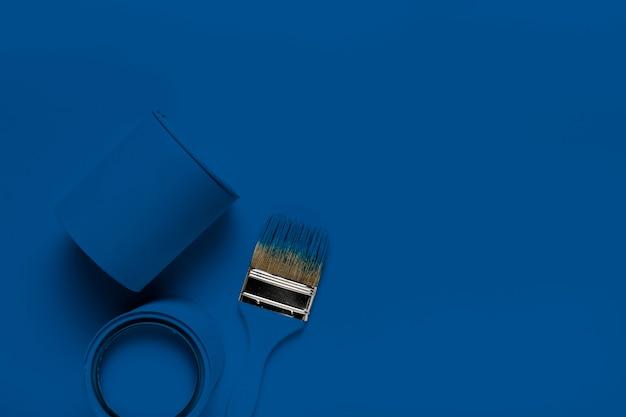 Pincéis de vista superior com lata de tinta azul clássica