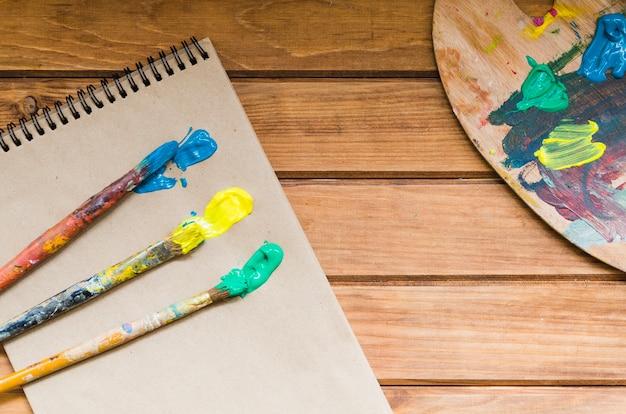 Pincéis de vista superior com tinta no caderno
