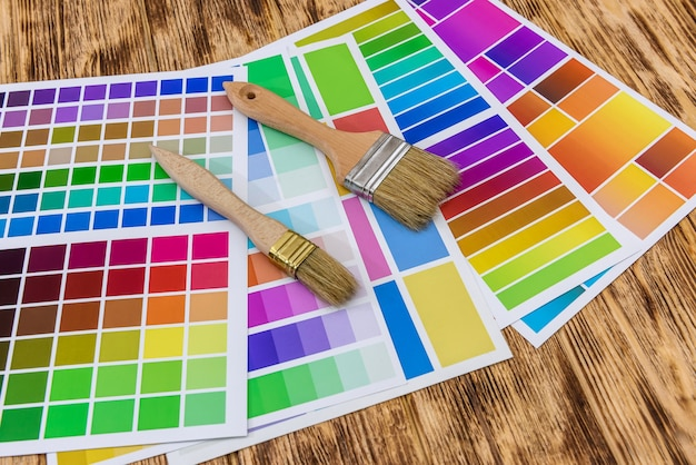 Pincéis e amostras de paleta de cores de tinta em fundo de madeira, close-up