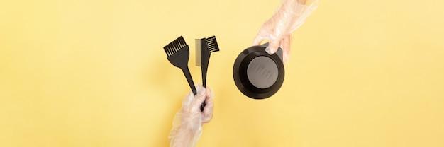 Pincéis e tigela para tingimento de cabelo em casa ou salão de beleza nas mãos de uma mulher com luvas em fundo amarelo