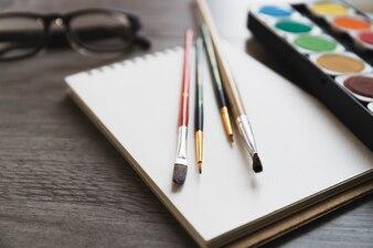 Pincéis e tinta perto de caderno de desenho
