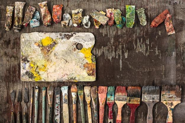 Pincéis e tubos de tintas a óleo na mesa de madeira