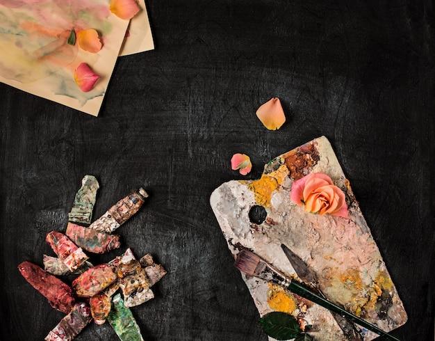 Pincéis e tubos de tintas a óleo na parede de madeira