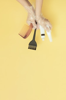 Pincéis e tubos para tingimento de cabelo em casa ou salão de beleza nas mãos de uma mulher com luvas em fundo amarelo com espaço de cópia foto vertical