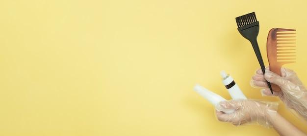 Pincéis e tubos para tingir o cabelo com as mãos enluvadas em um fundo amarelo com espaço de cópia