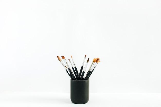 Pincéis em frasco na mesa. conceito de artista mínimo