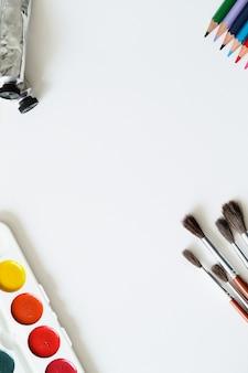 Pincéis, lápis e aquarelas, vista superior fundo