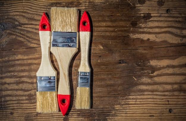 Pincéis para desenhar diferentes tamanhos em um fundo de madeira com espaço de cópia.