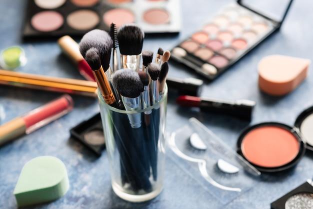 Pincéis para maquiagem estão sobre a mesa, onde ficam os cosméticos decorativos