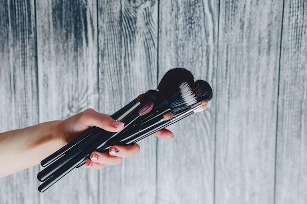 Pincéis para maquiagem nas mãos em fundo de madeira
