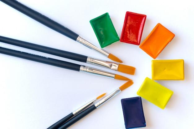 Pincéis para pintura de cor de água close-up e conjunto de tintas aquarela