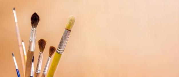 Pincéis para tintas em um fundo laranja. panorama. copie o espaço