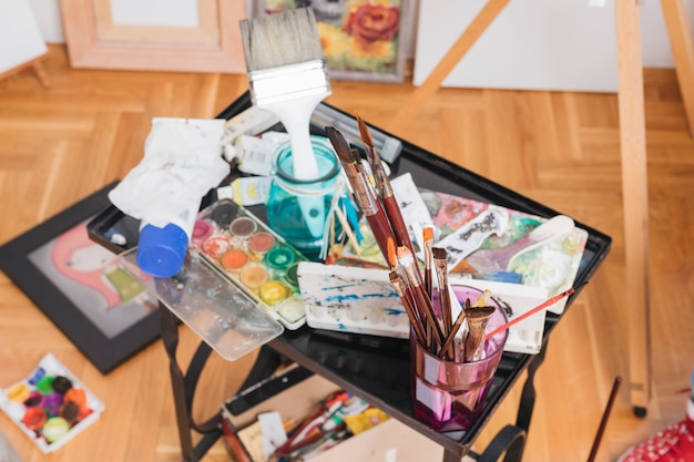 Pincéis usados e tintas abertas colocadas na mesa preta