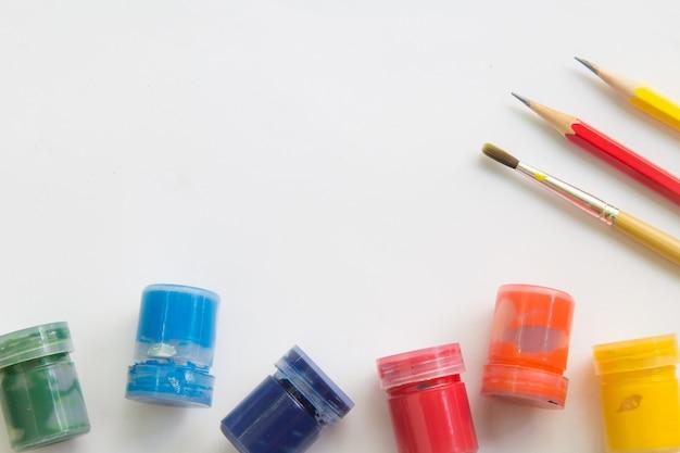 Pincel, aquarela, lápis em papel branco e espaço de trabalho para mensagem de texto.