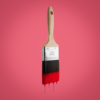 Pincel carregado com a cor vermelha que goteja fora das cerdas isoladas no fundo vermelho.