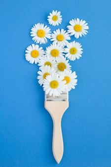 Pincel com camomilas no fundo azul. vista do topo. copie o espaço. conceito de flores de verão.