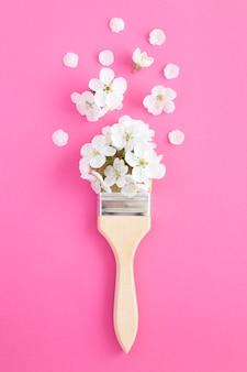 Pincel com flores brancas na superfície rosa