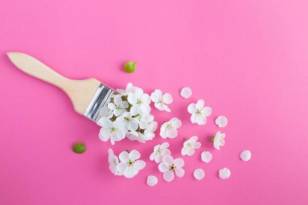 Pincel com flores brancas no fundo rosa
