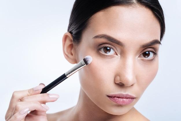 Pincel de alta qualidade. o close up de uma linda mulher de cabelos escuros e olhos escuros segurando um pincel de maquiagem perto do rosto enquanto posa
