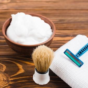 Pincel de barba sintética; espuma e navalha no guardanapo branco dobrado sobre a mesa de madeira