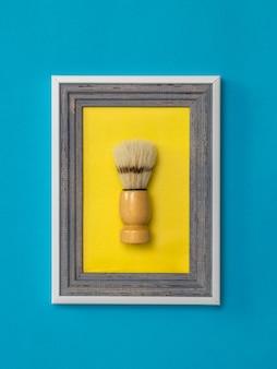 Pincel de barbear barbear em uma moldura em um fundo amarelo em uma parede azul. o conceito de cuidados com o corpo. higiene. minimalismo.